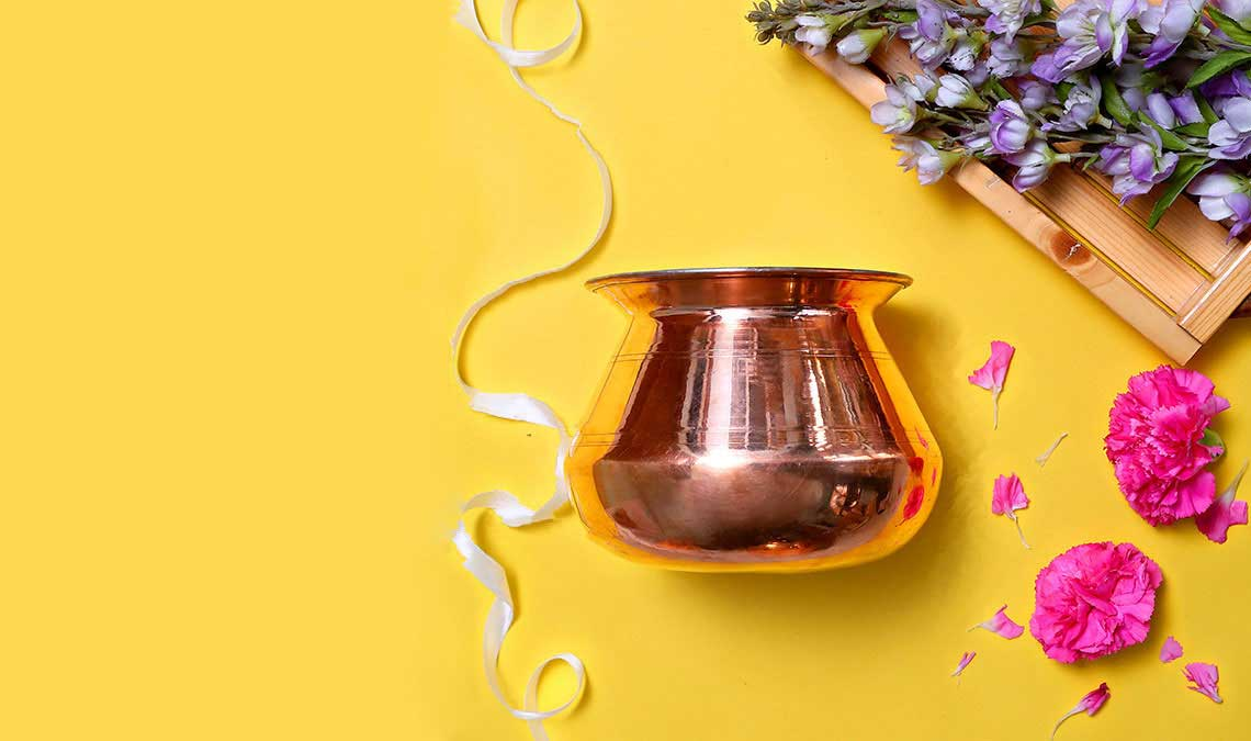 Copper pot in yellow background with wood and flowers